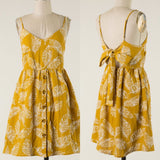 How adorable is this dress??!! This trendy mustard palm print sweet dress has a button front closure, adjustable straps for length and support and back self tie for more support and even cuter style.