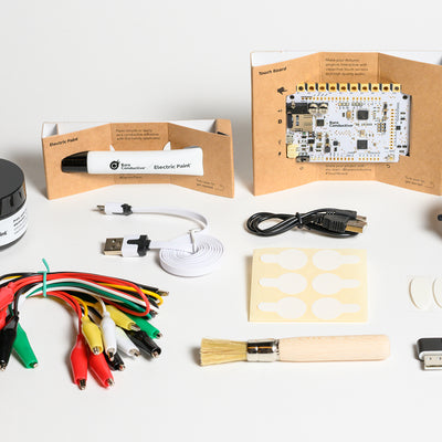 BARE Touch Board Starter Kit - Full view of inside content includes: 10 ml and 50 ml pot of electric paint, brush, cable testers, mini aligator lead cable set, two usb cable, mother board among others.