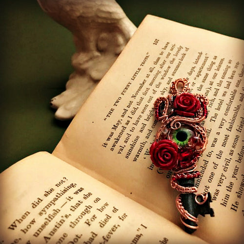 skeleton key pendant with copper weave, red roses, eye cabachon on open book with green background