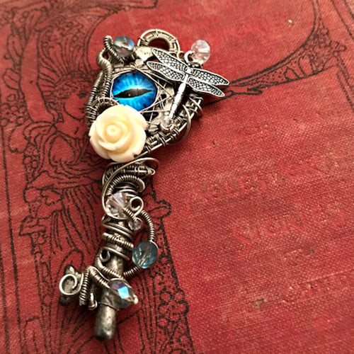 silver rose skeleton key pendant on red cloth covered book