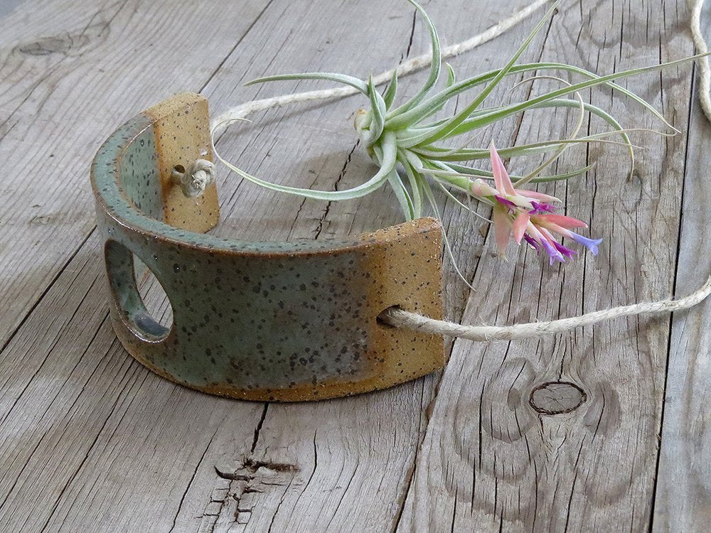 A green ceramic air plant hanger rests sideways on a wooden table next to a flowering air plant.