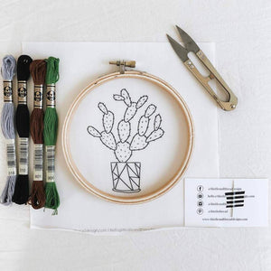 Cactus embroidery kit with thread, hoop, thread snips, and needle taped to a business card.