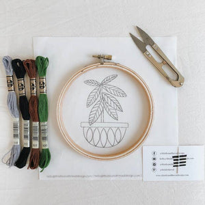 Image of an embroidery kit showing thread, hoop, fabric, thread snips, and a needle taped to a business card