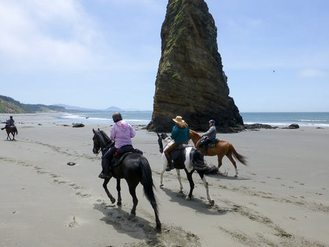 Riders go past The Needle at Cape Blanco State Park