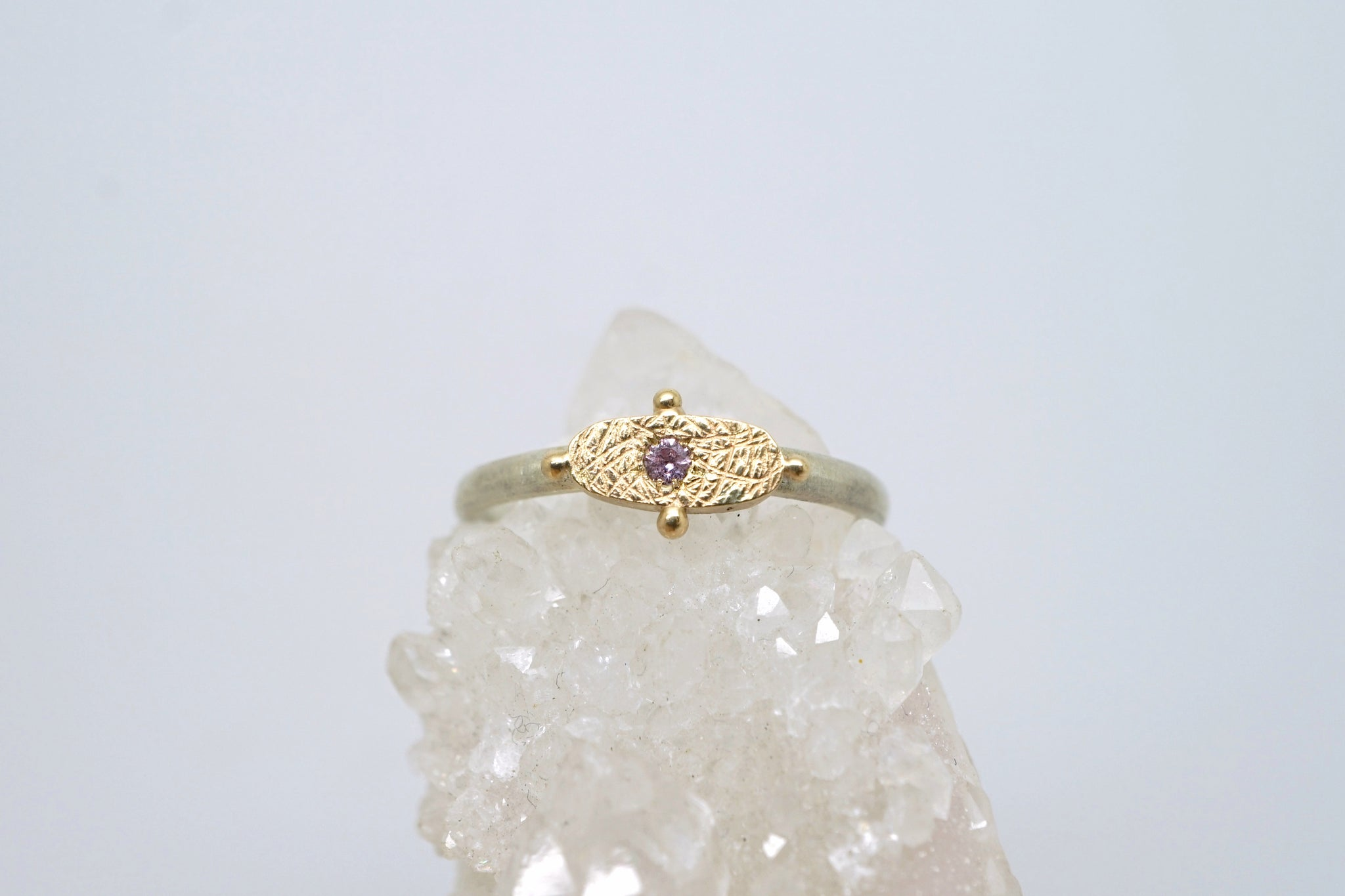 Textured emblem ring with pink sapphire