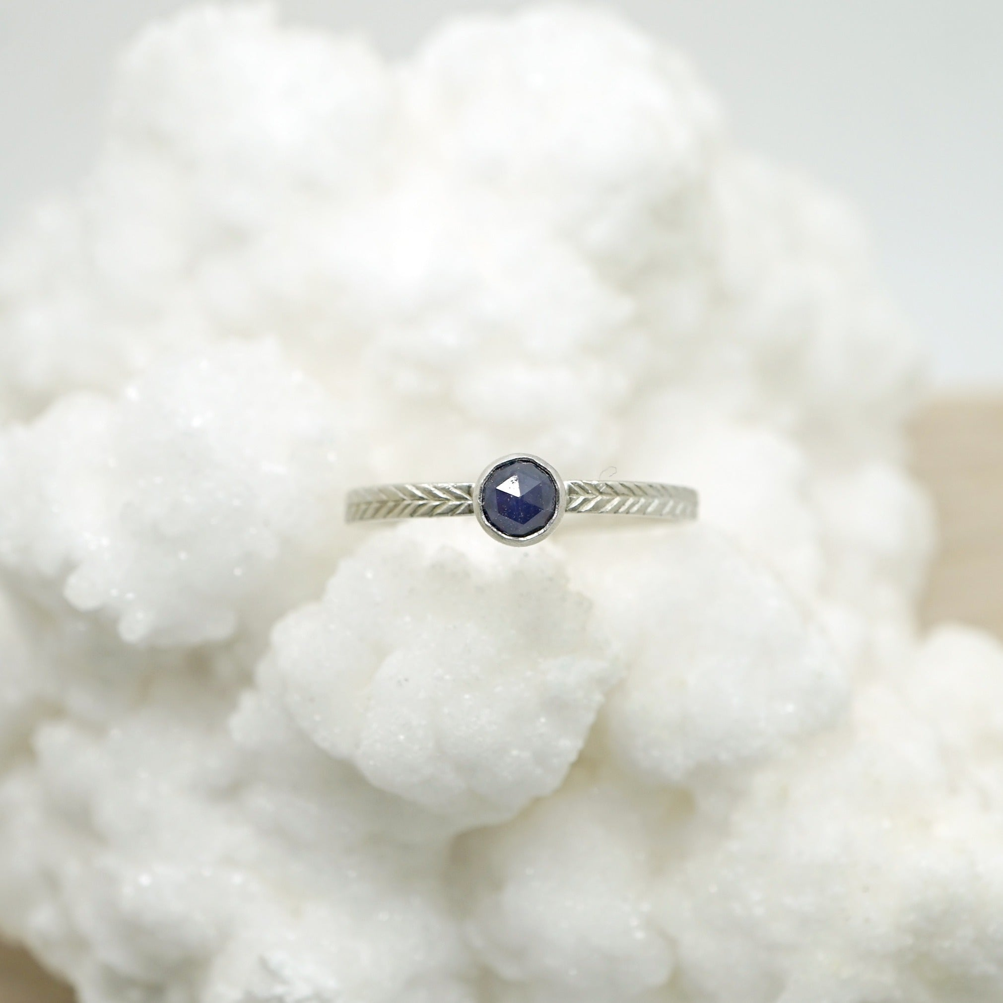Sapphire ring with hand-carved feather textures