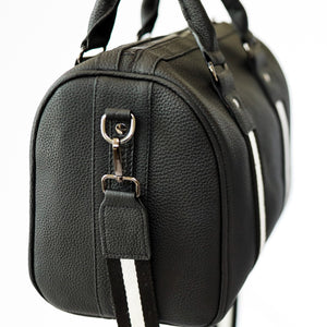 Black premium leather sports bag with black and white leather trim webbing. Long over shoulder black and white webbing strap attached to gunmetal black hardware.