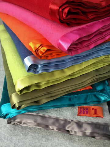 Stack of eight folded fleece blankets with matching satin trimmed edges. From top to bottom, the colours are: red, candy pink, bright (not fluorescent) orange, new blue, apple green, heather green, teal and light grey.  - isabee.co.uk