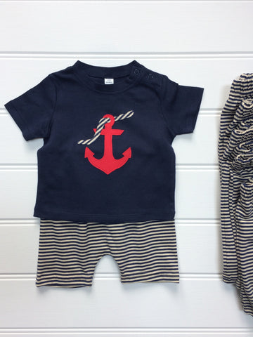 Dark blue cotton T-shirt partially laying on top of a pair of striped cream and navy shorts. T-shirt features an appliquéd red Anchor design, entwined with a striped rope. The clothes lay on a white panneled background. - isabee.co.uk