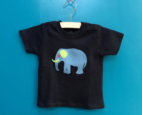 Black cotton short-sleeved t-shirt featuring an appliquéd meadow blue elephant with green and red accents. There are two subtle poppers (a.k.a. snaps) one shoulder of the top. T-shirt is displayed on a hanger in front of a teal background. - isabee.co.uk