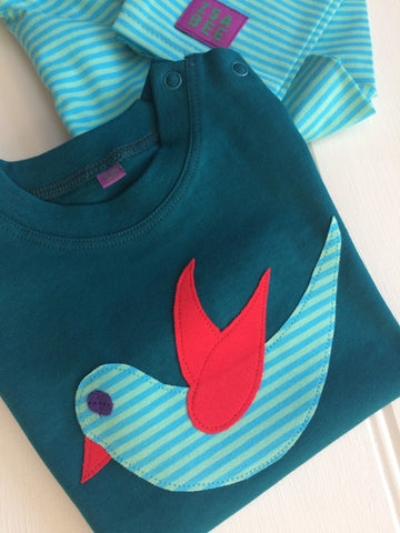 Teal coloured cotton T-shirt for babies aged 3-24 months with hand applique bird design on the front, side on in flight. The cute Baby Bird in turquoise and green stripe has red wing and beak detail and a purple eye - all hand sewn. Shoulder poppers on the neck for easy wear.  The T-shirt is folded and on top of a pair of folded Isabee turquoise and green stripy leggings which match the T-shirt. Designed and made in the Isabee London studio.
