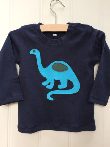 Blue long-sleeve organic cotton t-shirt for babies with turquoise hand-applique dinosaur with grey eye and detail. Two poppers on the shoulder for easy wear. The top is on a hanger with a white background. Hand made in the Isabee London studio.