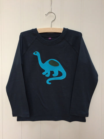 Dark blue long-sleeved t-shirt with a turquoise hand-applique dinosaur on the front with grey eye and body detail. This organic cotton top for children is on a hanger with a which background. Made by Isabee in London.