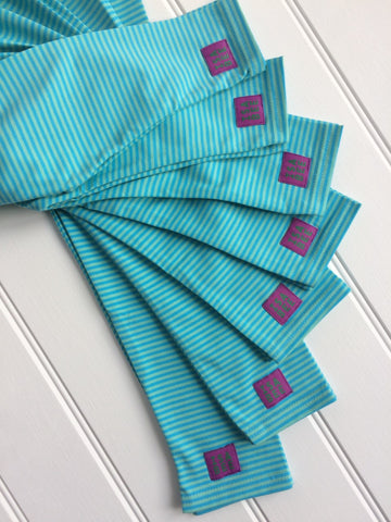 Fan display showing 7 pairs of turquoise and green stripy leggings with elasticated waist and purple and green Isabee label at ankle end, on white background. Cotton jersey leggings for kids and babies made in England by -isabee.co.uk