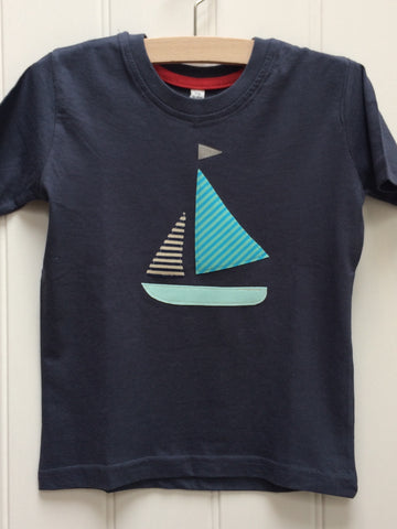 Dark blue cotton T-shirt featuring an appliquéd Sailing boat design with a light blue bottom, two stripy sails (one of which matches the shorts, the other in pale greeny-blue shades) and a reflective flag. The t-shirt is mounted on a hanger against a white panneled background. - isabee.co.uk