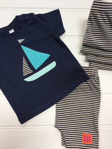Dark blue cotton T-shirt diagonally laying across of a folded pair of striped cream and navy shorts. Shorts have small orange and purple ISABEE logo. T-shirt features an appliquéd Sailing boat design with a light blue bottom, two stripy sails (one of which matches the shorts, the other in pale greeny-blue shades) and a reflective flag. A small stack of folded shorts sits next to them. The clothes lay on a white panneled background. - isabee.co.uk