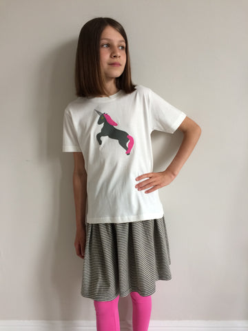 Young girl wearing a cream coloured cotton children's t-shirt featuring an olive coloured appliquéd Unicorn design with a reflective horn and a bubblegum pink mane and tail. Unicorn is rearing on its hind legs. Girl wears matching grey skirt and pink leggings and stands, with one hand on her hip, in front of a white wall. - isabee.co.uk