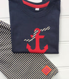Folded dark blue cotton T-shirt partially laying across of a folded pair of striped cream and navy shorts. Shorts have small orange and purple ISABEE logo. T-shirt features an appliquéd red Anchor design, entwined with a striped rope. The clothes lay on a white panneled background. - isabee.co.uk