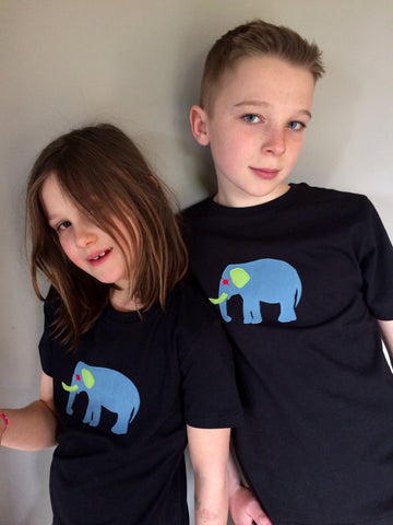 Girl and boy wearing Black cotton t-shirts featuring an appliquéd, meadow blue elephant with green and red accents. The two children lean against each other smiling at the camera. - isabee.co.uk