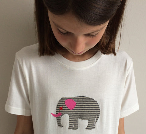 Girl looking down at the t-shirt she is wearing. Cream coloured t-shirt featuring an appliquéd, grey striped elephant with pink and red accents. Off-white wall behind model. - isabee.co.uk