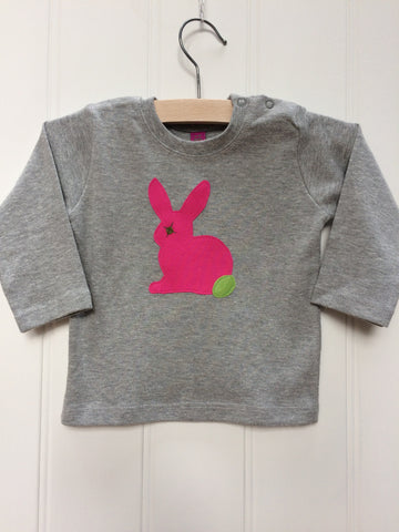 Baby Rabbit long-sleeved t-shirt on a hanger.  The top is a soft grey colour and  features an applique rabbit in fuschia pink with a leaf green tail and eye detail. Shoulder poppers on one side for easy wear. Hand made by Isabee in London.