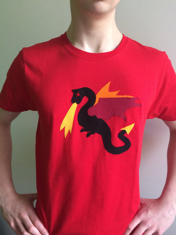 Adult's Red organic cotton T-shirt featuring a Black Appliqué Dragon with fiery red, orange and yellow detailing. T-shirt is worn by a young man with his hands on his hips.- isabee.co.uk