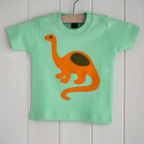 Baby Dinosaur T-shirt - mint-green t-shirt featuring an orange dinosaur with olive details. T-shirt has two poppers on the shoulder. It is displayed in a hanger in front of a white panelled background. - isabee.co.uk