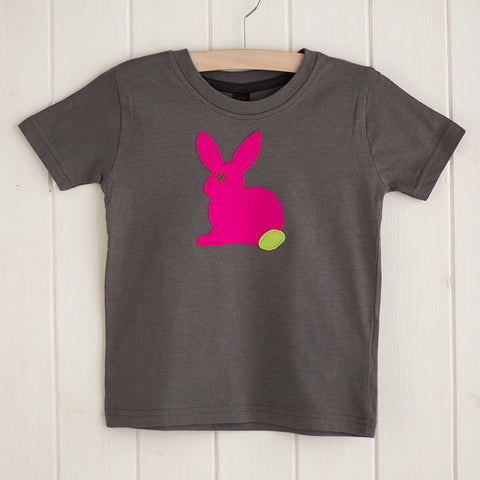 Dark grey children's t-shirt featuring a fuchsia pink appliqued rabbit with a leaf green tail. T-shirt is displayed on a hanger in front of a white panelled background. - isabee.co.uk