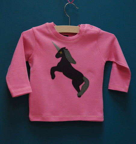 Bubblegum pink baby's long sleeved t-shirt featuring an augergine coloured Appliquéd Unicorn design with a reflective horn and a olive green mane and tail. Unicorn is rearing on its hind legs. There are two poppers on the shoulder of the top. T-shirt is on a hanger in front of a teal background. - isabee.co.uk