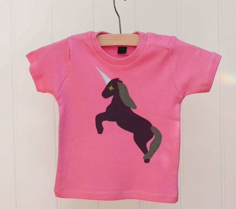 Bubblegum pink baby's t-shirt featuring an augergine coloured Appliquéd Unicorn design with a reflective horn and a olive green mane and tail. Unicorn is rearing on its hind legs. There are two poppers on the shoulder of the top. T-shirt is on a hanger in front of an off-white panneled background. - isabee.co.uk