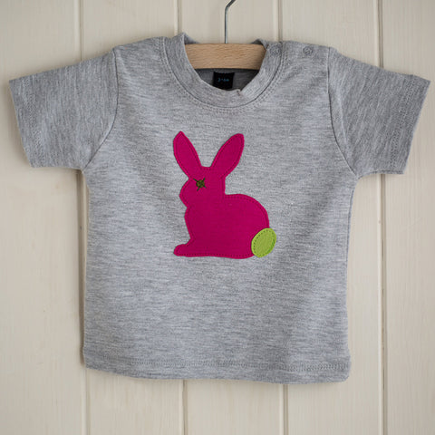 Light grey melange baby's t-shirt featuring a fuchsia pink appliqued rabbit with a leaf green tail. There are two poppers on the t-shirt's shoulder. T-shirt is displayed on a hanger in front of a white panelled background. - isabee.co.uk
