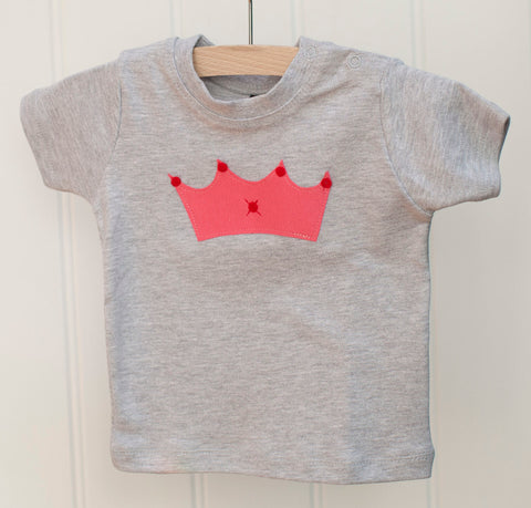 Grey melange baby t-shirt featuring a pink crown design with red details. T-shirt has poppers on the shoulder for easy wear. T-shirt hangs against a white panneled background. - isabee.co.uk