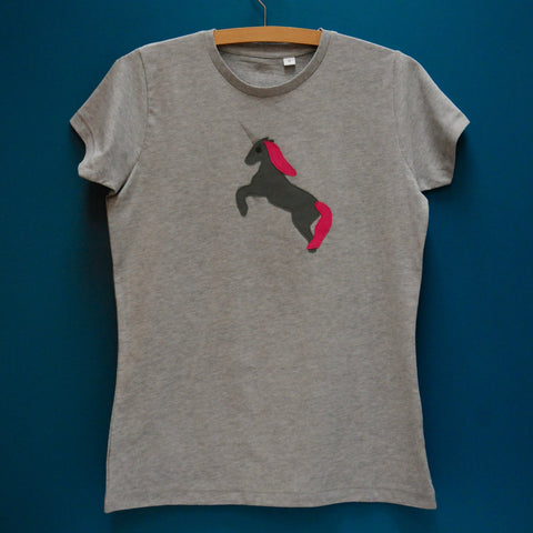 Grey melange fitted tshirt. Slim fit or women's fit with cap sleeves. T-shirt features a dark grey Appliquéd Unicorn design with a reflective horn and a pink mane and tail. Unicorn is rearing on its hind legs. T-shirt is on a hanger in front of a teal background. - isabee.co.uk