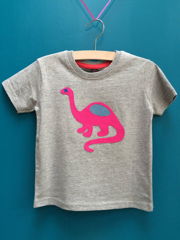 Children's light grey melange t-shirt featuring an appliquéd pink dinosaur with blue details. Dinosaur is reaching its long neck up and the tail is curved around beside. Displayed on a teal background. - isabee.co.uk