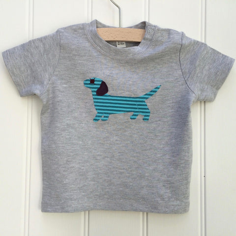 Light grey cotton melange t-shirt for babies with a cheerful applique dachshund sausage dog on the front. The dog is a teal striped with aubergine ear and eye detail. Two poppers on the shoulder for easy wear. T-shirt is displayed on a hanger against a white panelled background. - isabee.co.uk