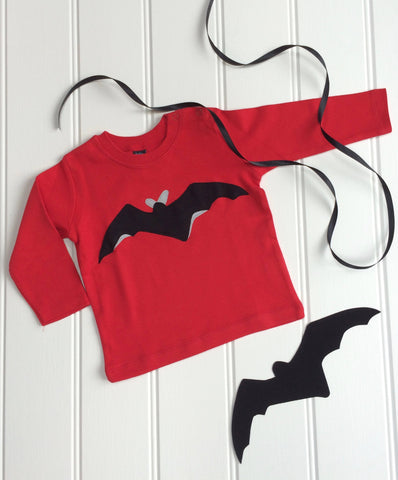 Red, long-sleeved baby t-shirt featuring a black bat design with reflective details. T-shirt is displayed on a white panneled background with a black bat and a black ribbon beside it. - isabee.co.uk