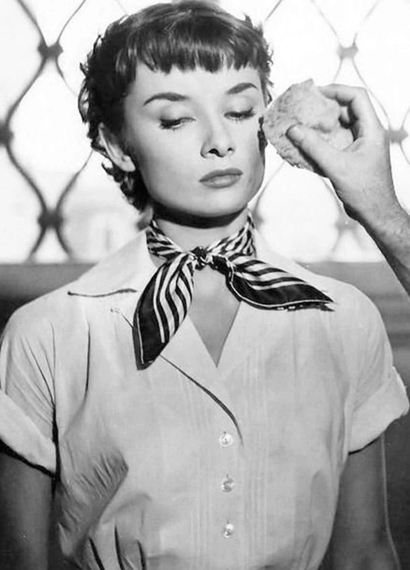 Audrey-Hepburn-wearing-a-white-shirt-and-silk-scarf-tied-around-her-neck-