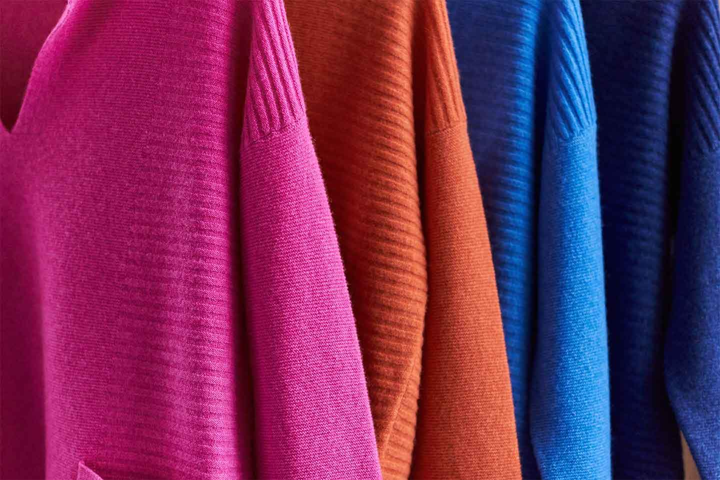 Cashmere jumpers in a range of colours hanging