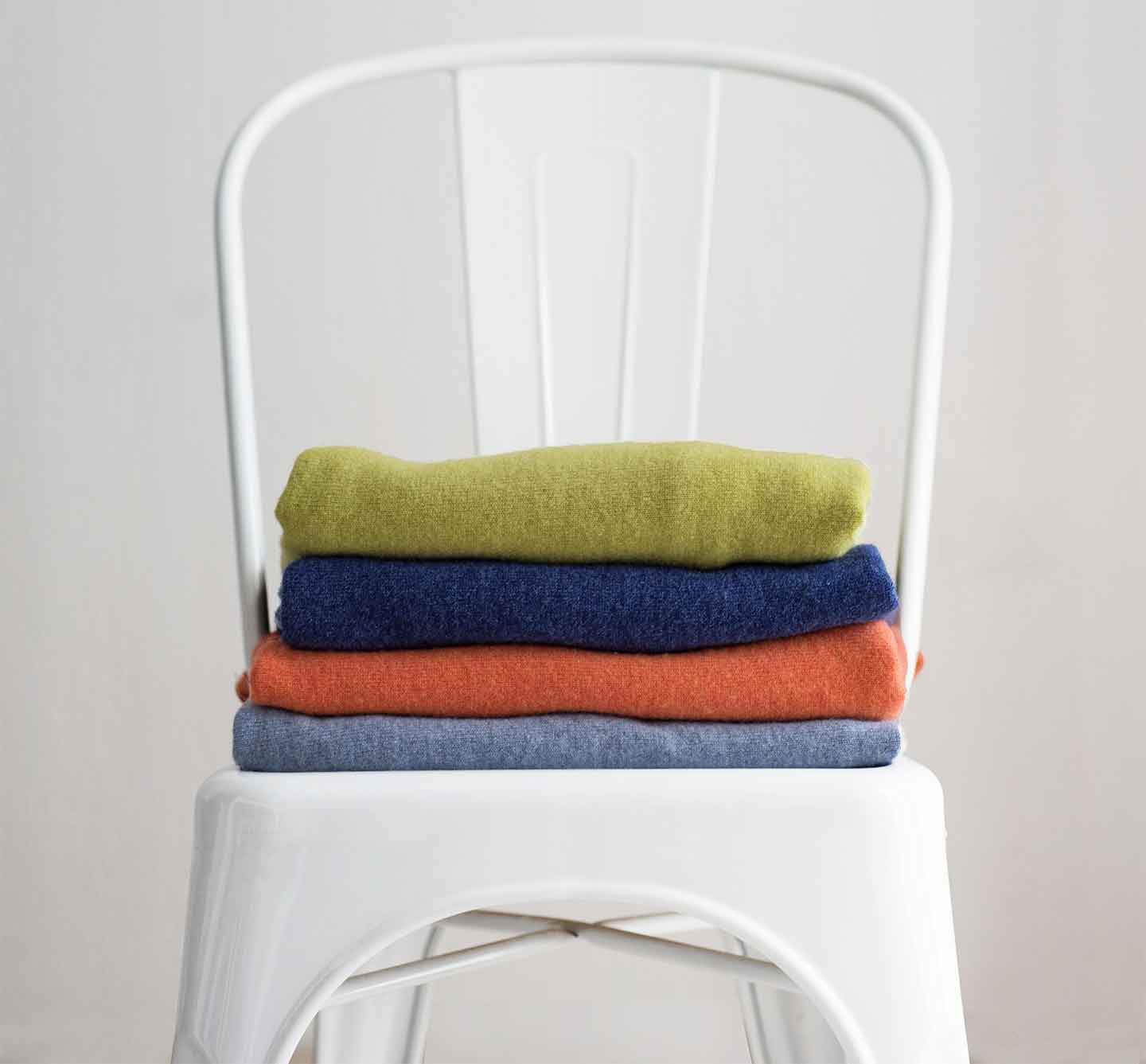 Folder-cashmere-jumpers-stacked-on-a-white-chair-in-front-of-a-white-wall