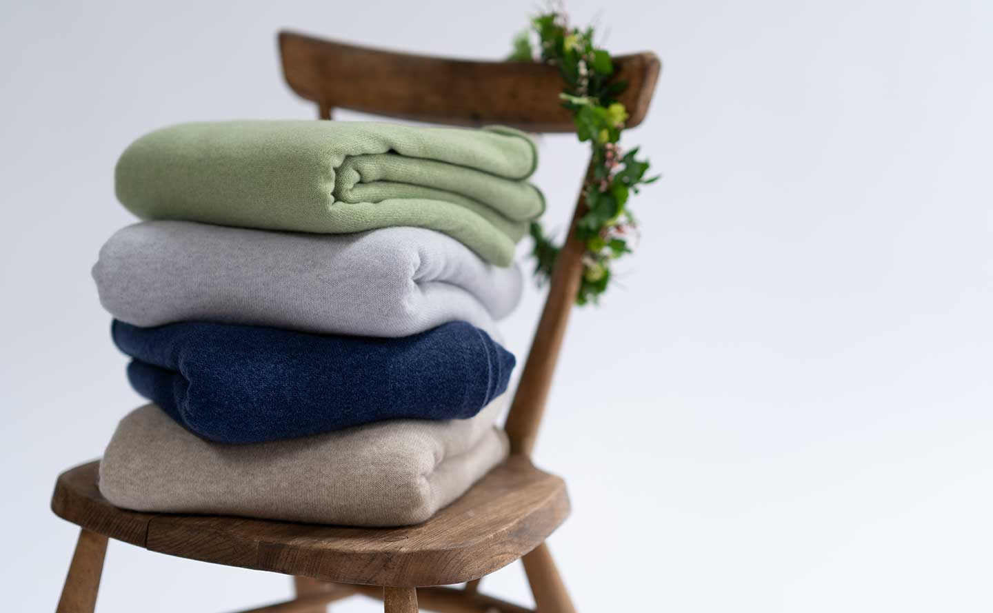 cashmere travel wraps piled up on wooden stool