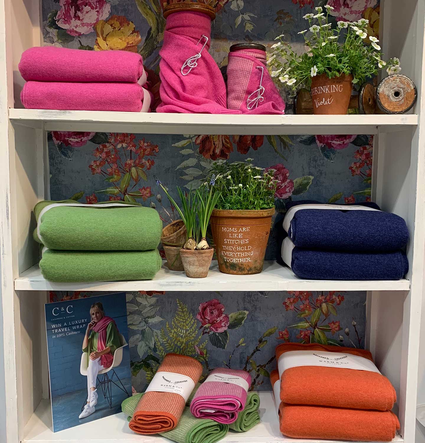 bright summer cashmere on shelves with flowers and floral background