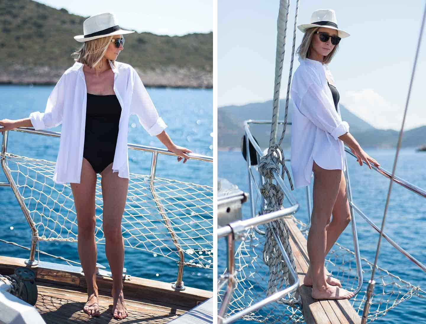Woman on a boat with sea surrounding wearing a black swimsuit sunglasses a hat and open white shirt