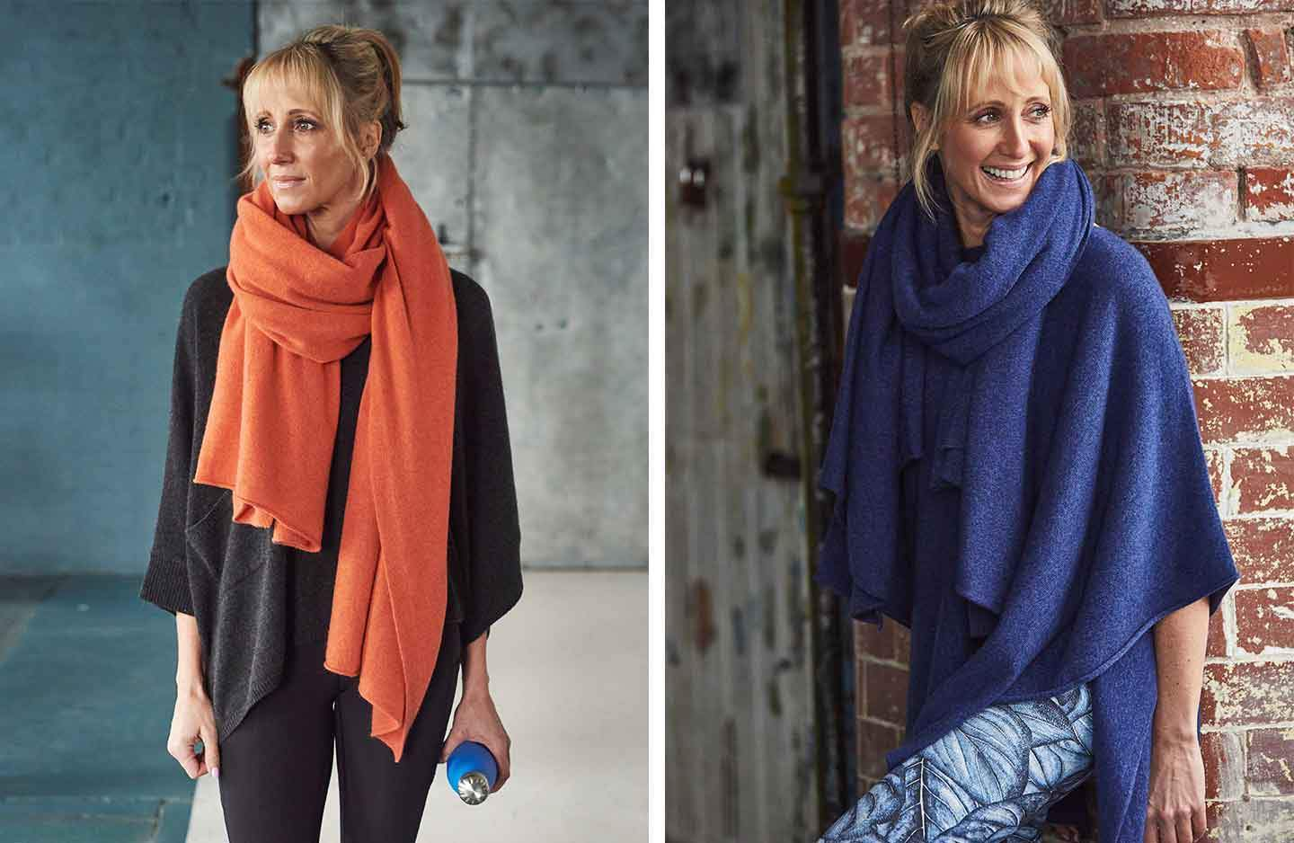 Women against brick wall in grey oversized cashmere poncho with orange cashmere scarf and women in blue cashmere poncho with blue cashmere scarf wrapped around neck