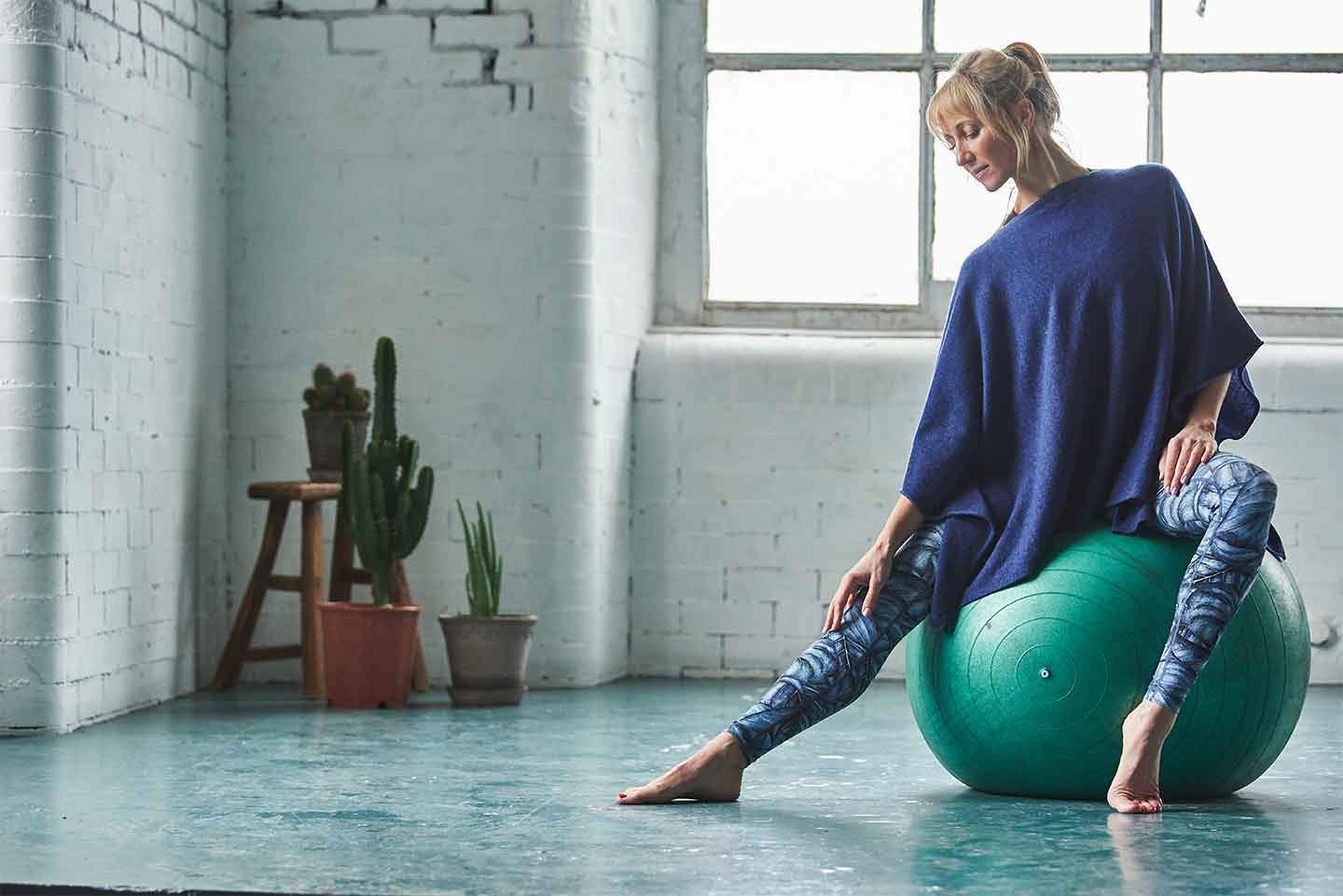 Women-doing-yoga-in-front-of-a-window-sat-on-a-yoga-ball-in-sportswear-and-blue-cashmere-poncho