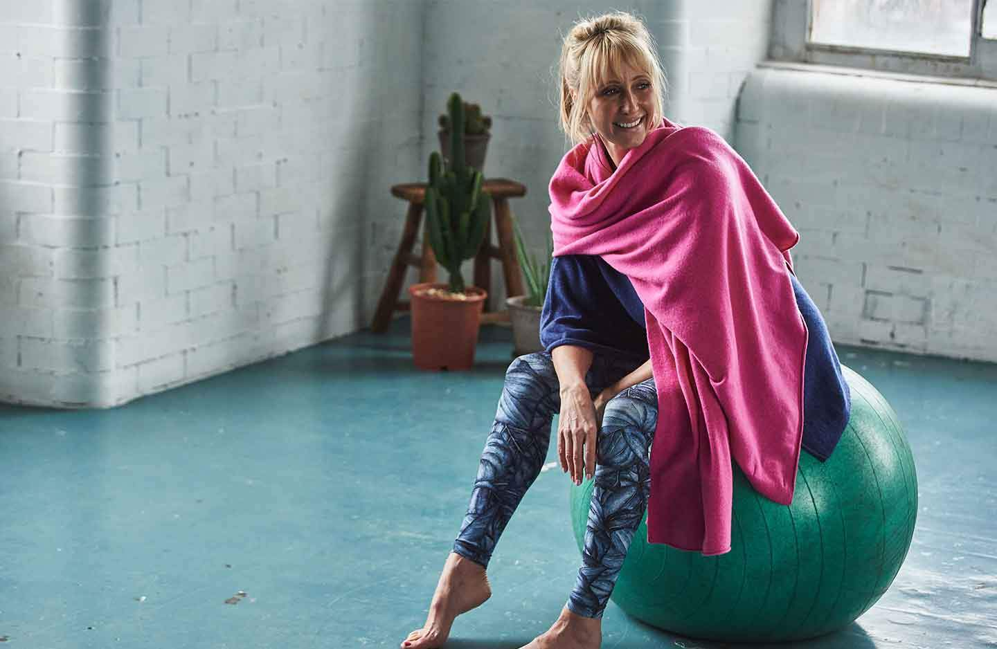 Women sat on green yoga ball in blue sportswear with a blue cashmere poncho layered over the top with a pink cashmere wrap wrapped around shoulders in building with white brick wall and windows with cactus and wooden stool in the corner