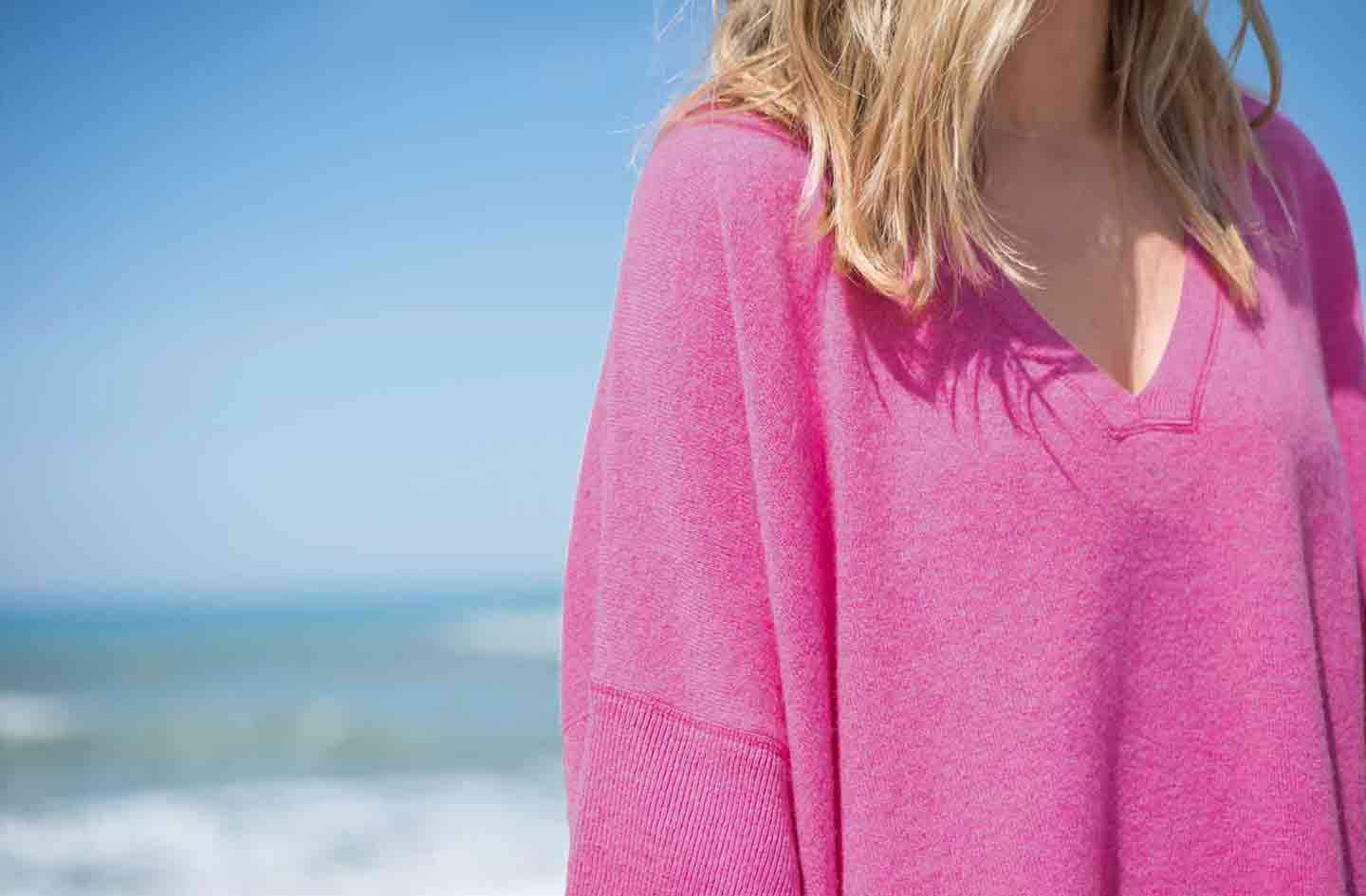 Women-standing-infront-of-the-sea-and-blue-sky-wearing-a-pink-cashmere-kimono-