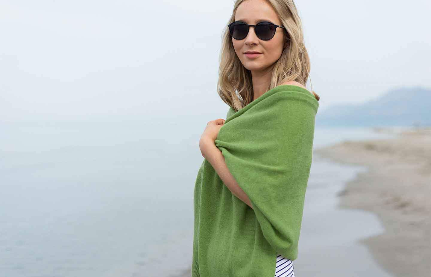 Women-standing-on-a-beach-with-blue-sky-in-the-background-wearing-sunglasses-and-clutching-a-green-cashmere-wrap-around-her-shoulders