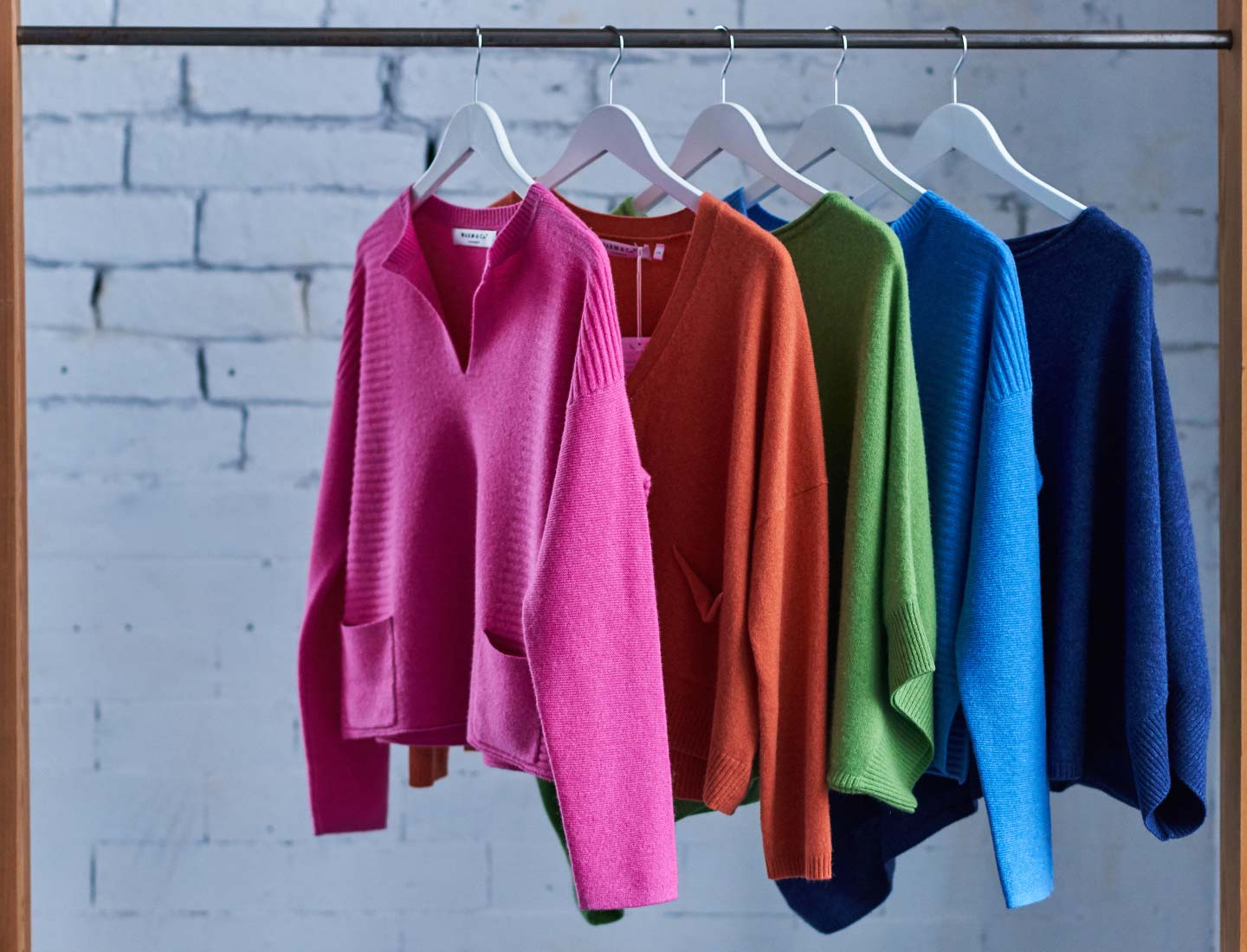 cashmere-jumpers-on-a-wooden-rail-in-a-warehouse