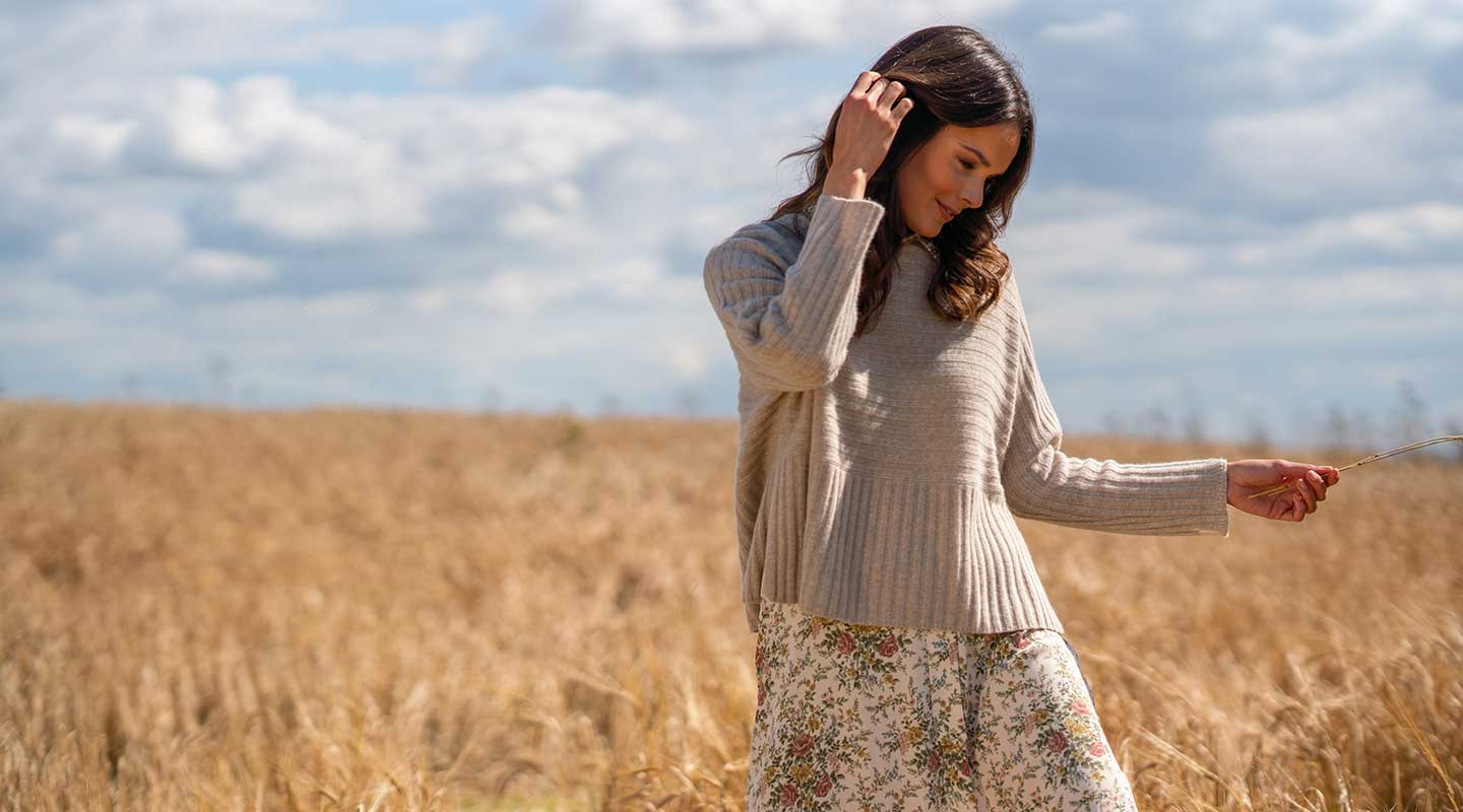 model in wheat field wearing neutral cashmere jumper
