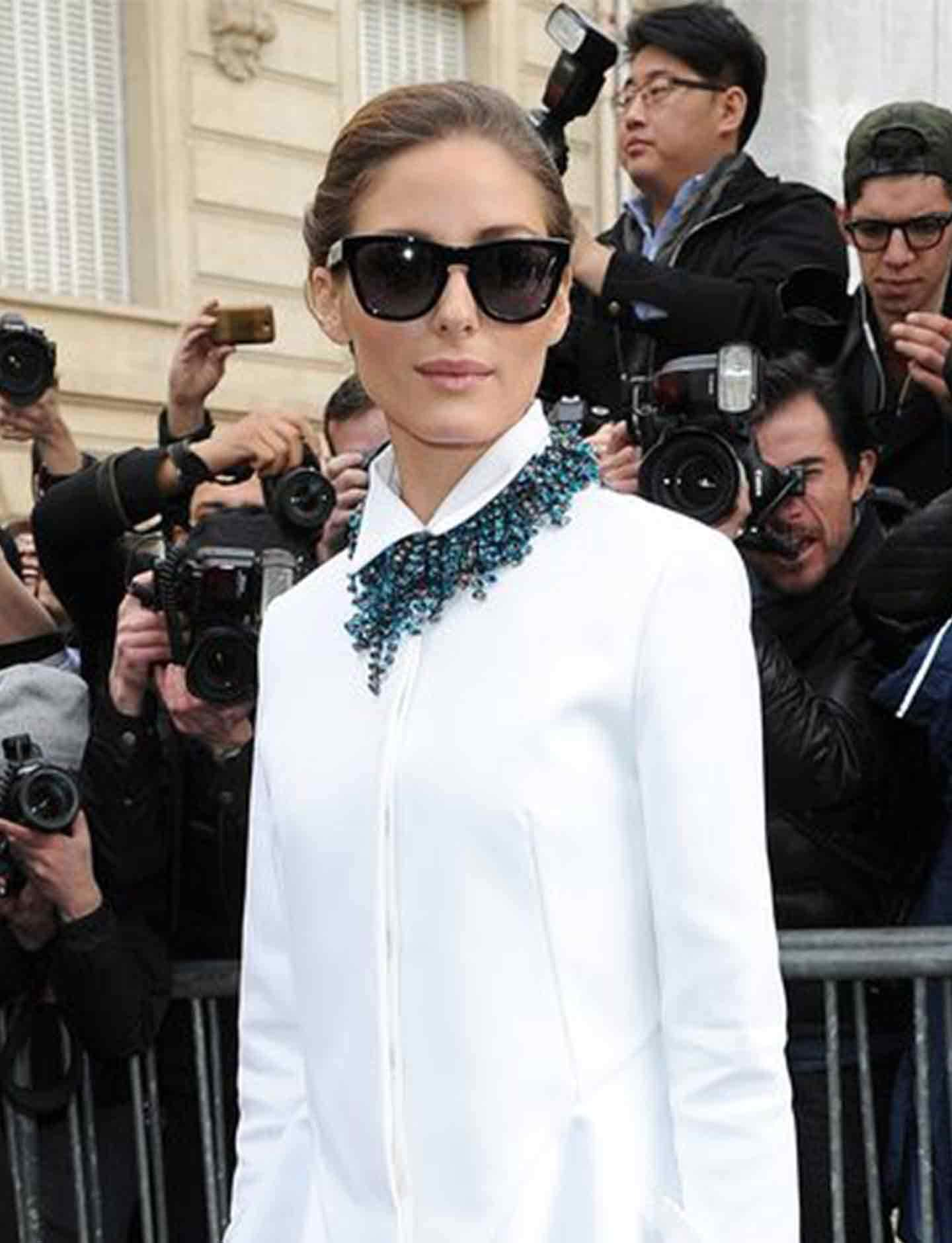 olivia palermo wearing white shirt dress and statement necklace standing in front of barriers and photographers
